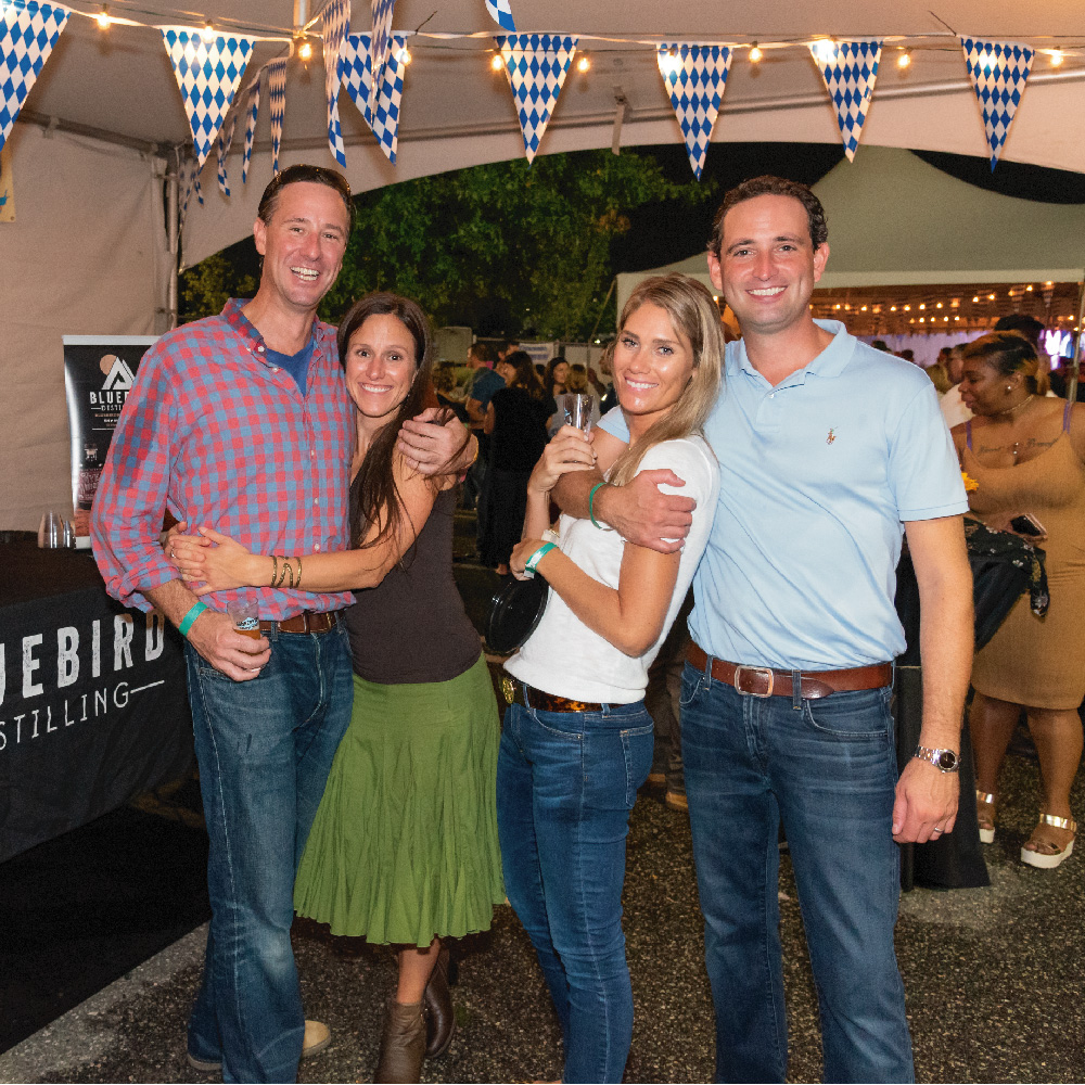 four people hugging and smiling for photo at beerfest